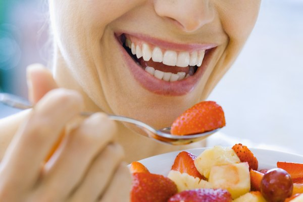 Woman smiling and eating fruit