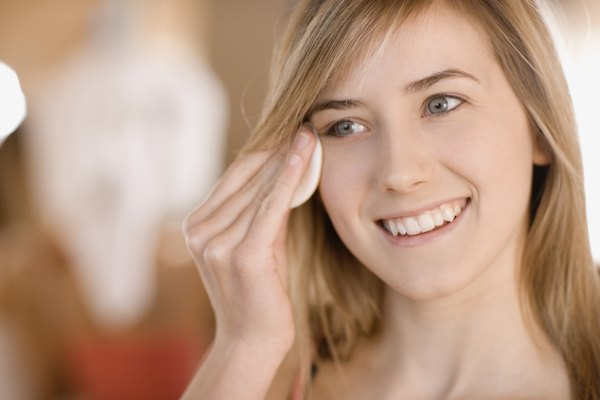 Teenage girl removing eye makeup