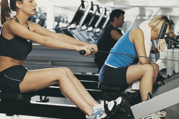 Three People Exercise on Rowing Machines, One Exhausted