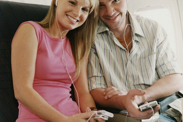 Portrait of a Couple Sitting on a Plane, Holding MP3 Players
