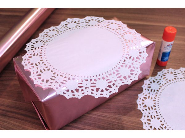 Adhere paper doilies to box