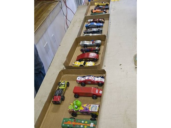 Pinewood derby cars sorted in boxes wait for their race.