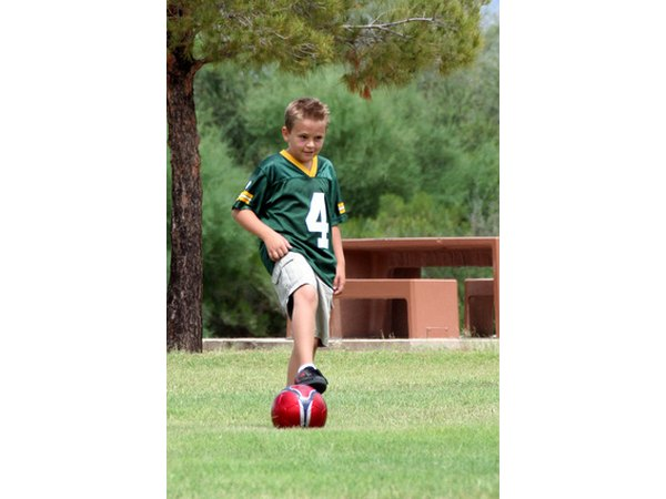 Show a young player how to stop the soccer ball with one foot.