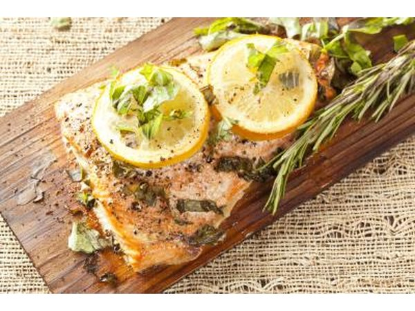 Grilled salmon with lemons and herbs on wood board