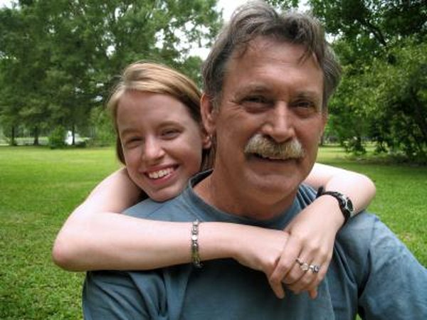 A teenager gives her dad a hug outside.