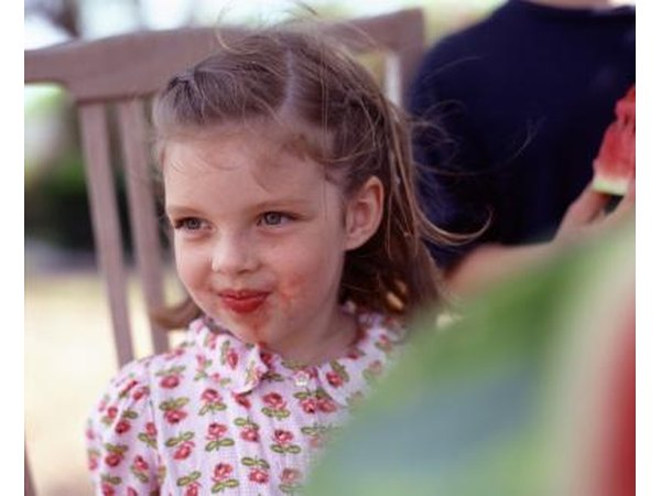 A little girl has red fruit on her chin.