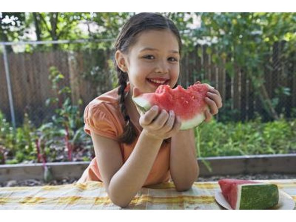 A little girl eating a slice of watermelon at an outdoor table near the garden.