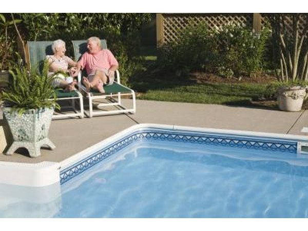 Senior couple sitting by swimming pool