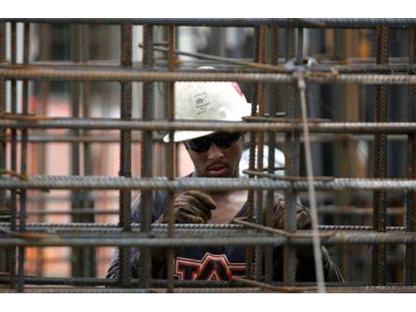 Construction worker attaches rebar at building site