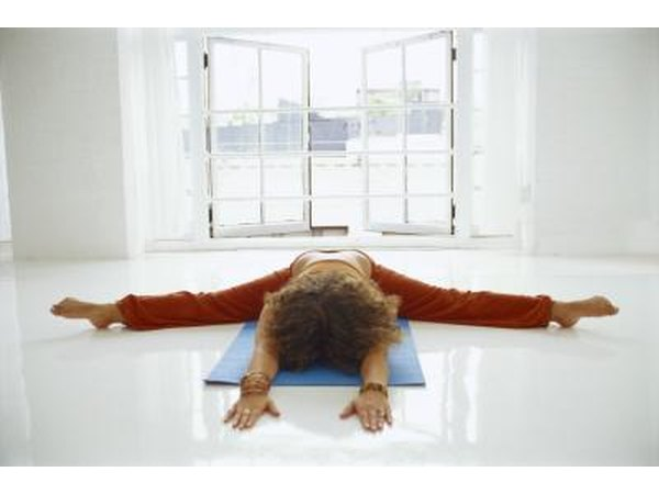 A woman does tortoise pose on a mat.