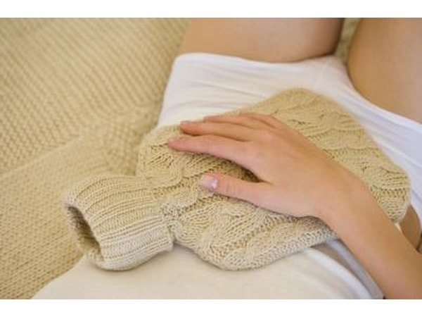 Woman holding hot water bottle on stomach