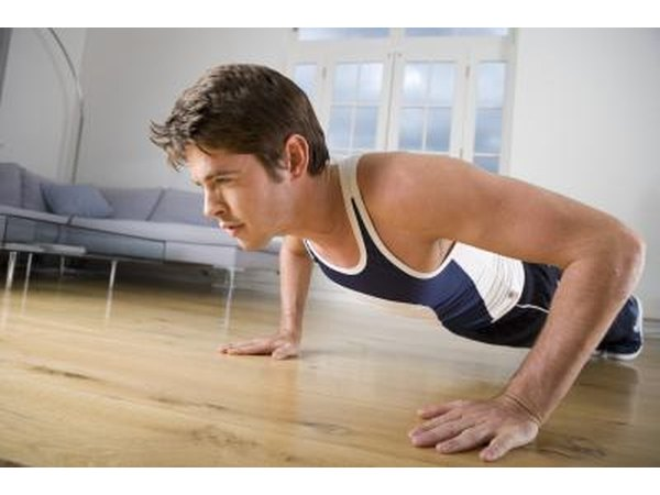 A man performs push ups from the comfort of his home.