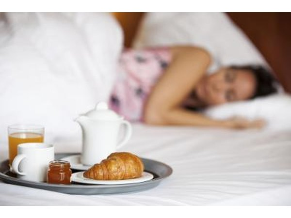 Woman lying in bed next to breakfast