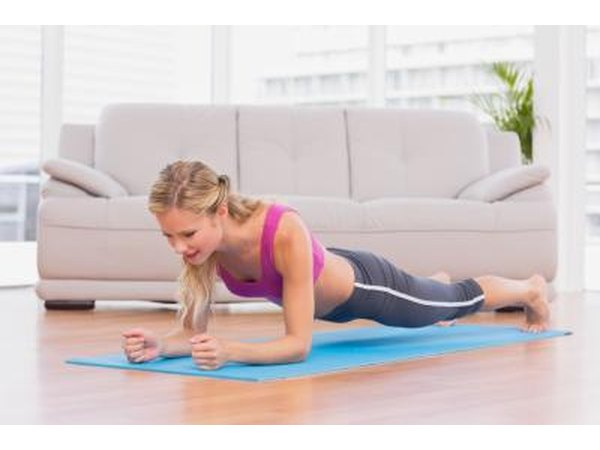 Young woman doing the plank position on yoga mat.