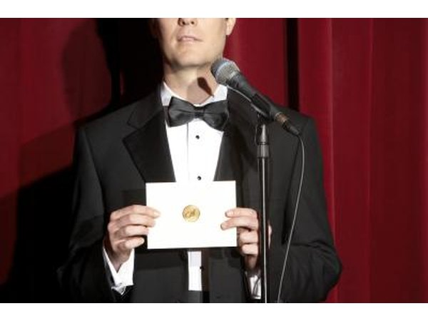 Man in tuxedo announcing award recipient