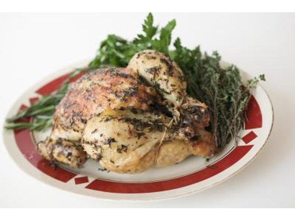 A roasted chicken with vegetables on a plate.