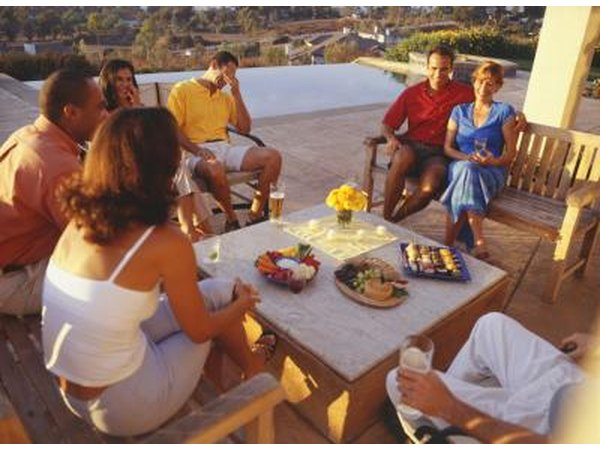 A group of friends relaxing on wooden patio furniture.