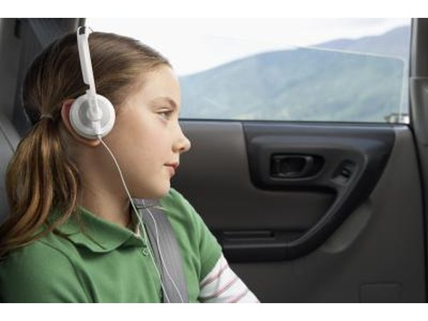 Young girl wearing headphones in a car.