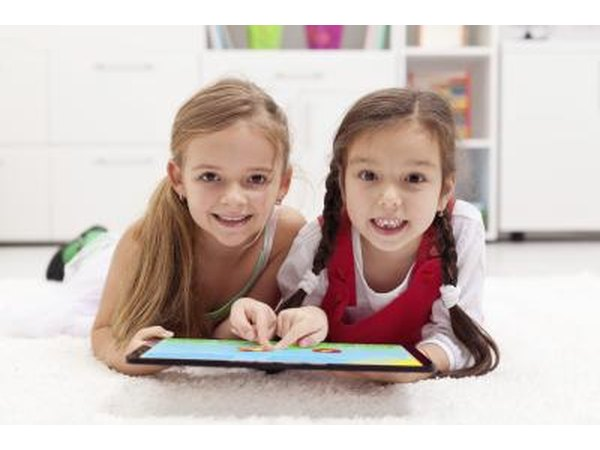 Two girls playing with computer tablet