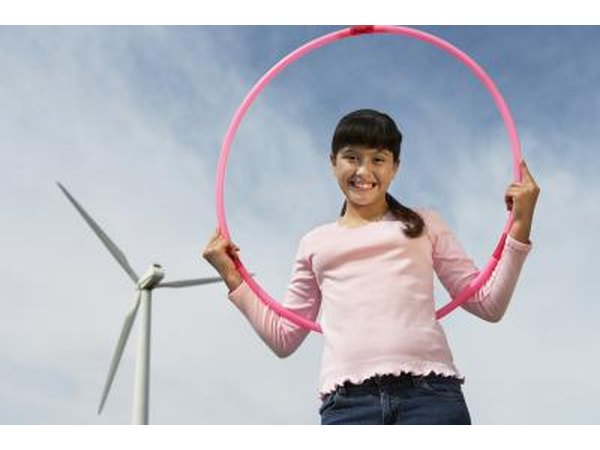 young girl holding hula hoop in field
