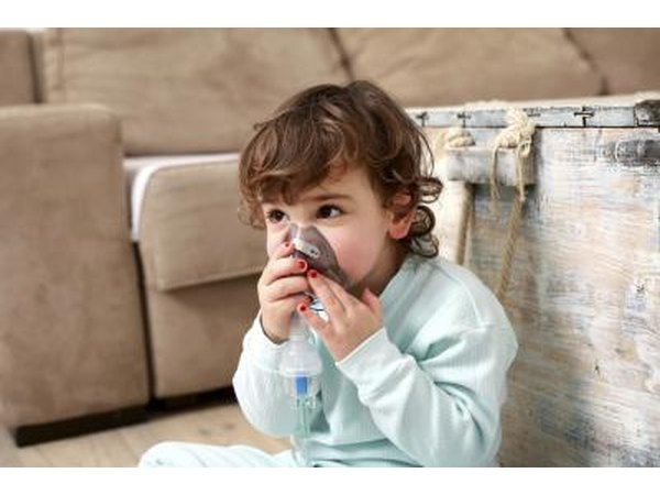 A small child uses an inhaler mask.