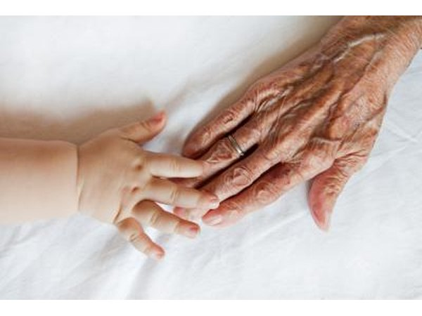 Baby touching Great Grandmothers hand