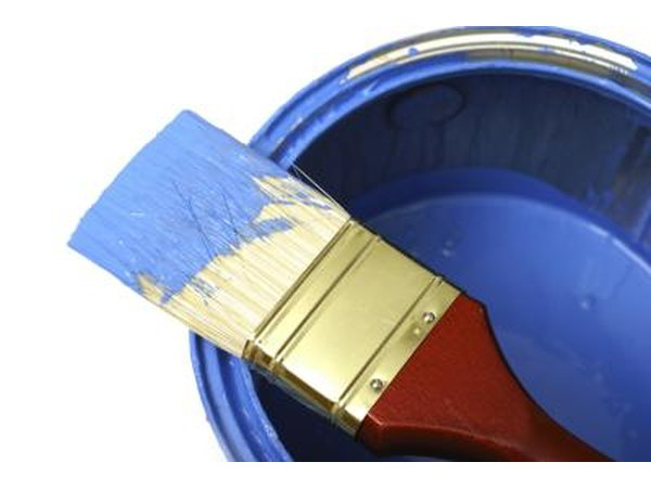 Paint can and paintbrush in blue paint.