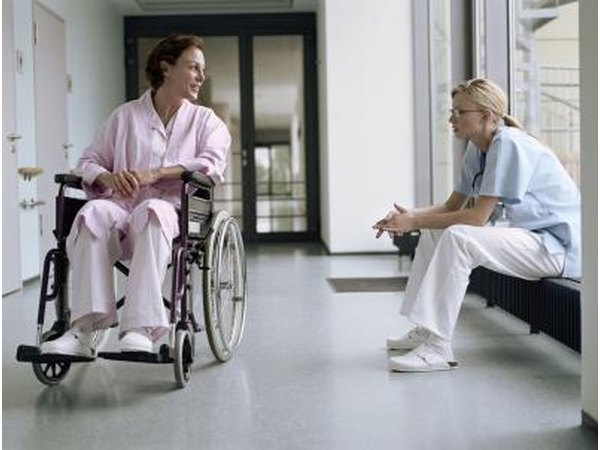 Nurse talking with patient in wheelchair.