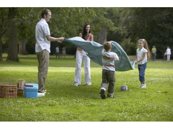 A family spreading out a picnic blanket in the grass