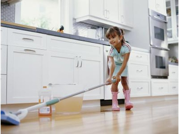 A young girl is cleaning a hardwood floor.
