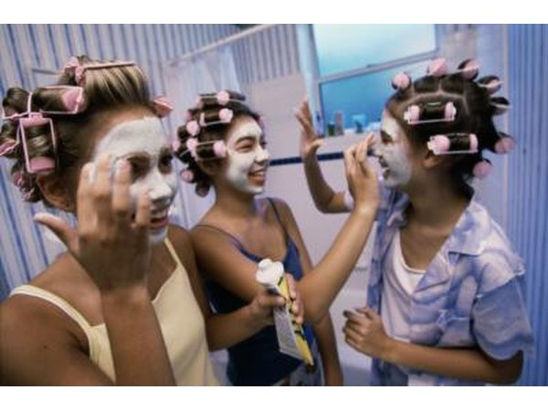 Teenage girls applying facial masks