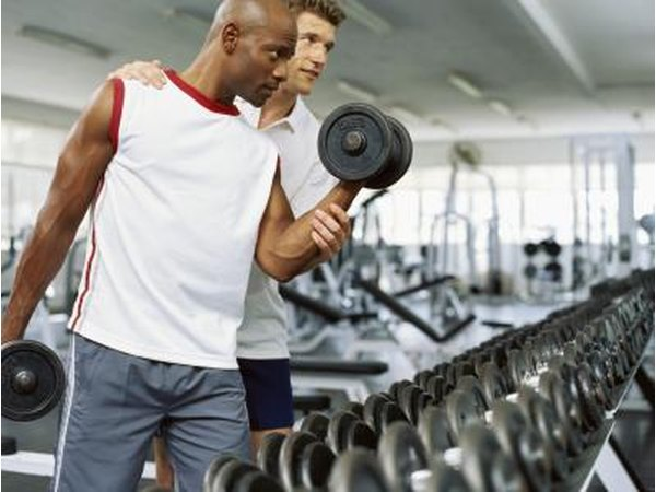 A man works with a personal trainer at a gym.