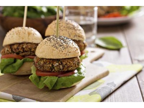 Vegetarian burgers on a bun with lettuce and tomato.