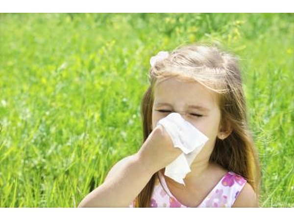 A girl blows her nose outside.