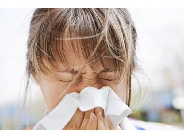 A woman blows her nose outside.