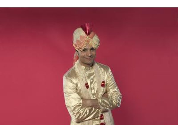 The Indian groom is clean shaven, dressed royally in rich fabrics and adorned in flower garlands.