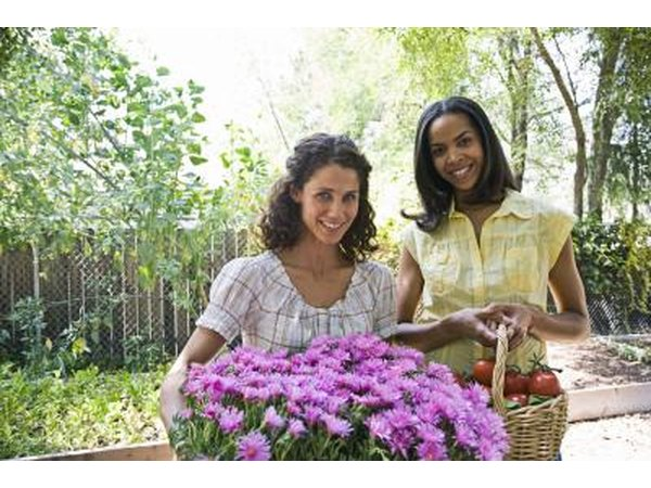 Women with flowers and produce from a garden.