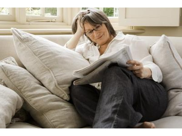 Woman reading paper on couch