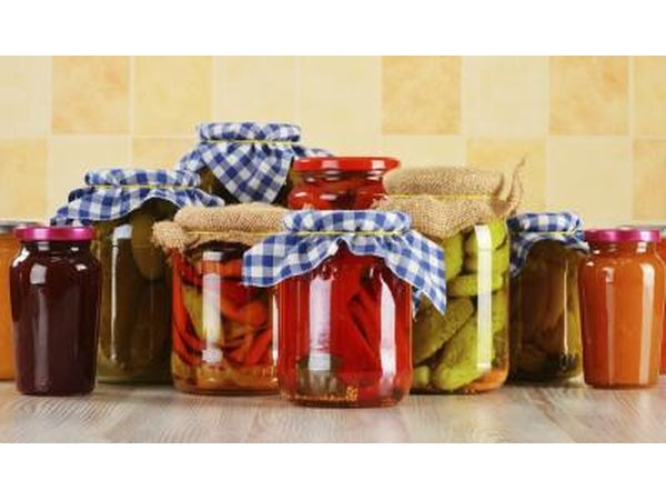 Glass jars filled with vegetables for fermenting.