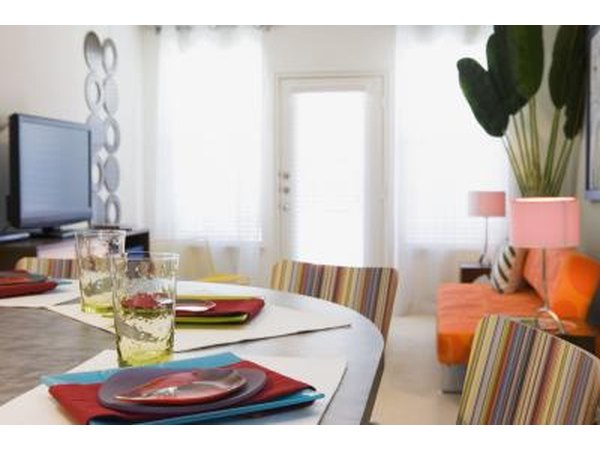 A dining room table is set with colorful accents that match the living room.