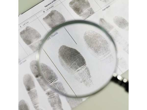 A magnifying glass over a fingerprint on paper.
