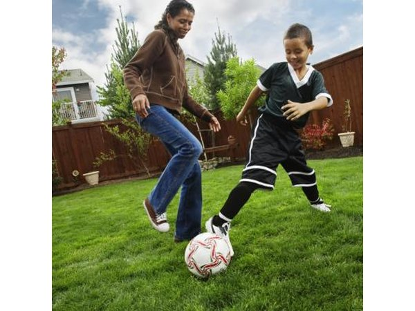Mother and son playing soccer in backyard