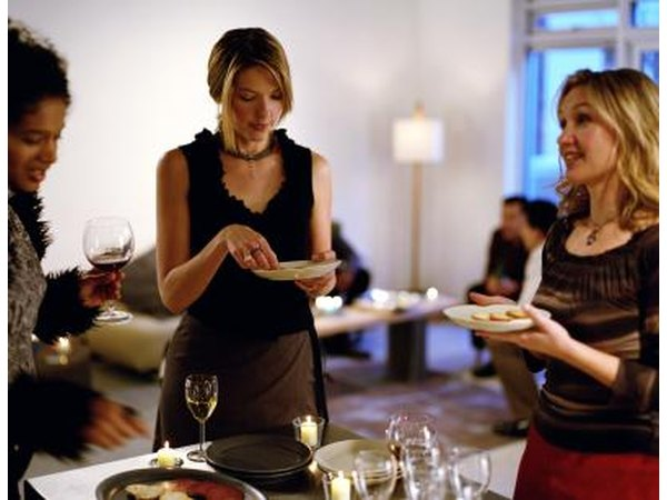 Women are holding plates and wine glasses.