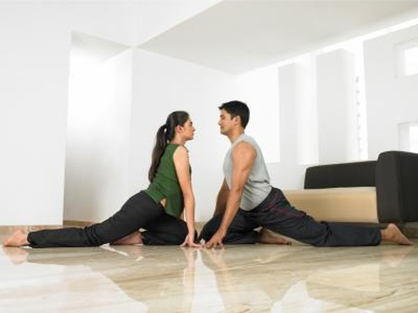 Man and woman doing One-Legged Pigeon pose.