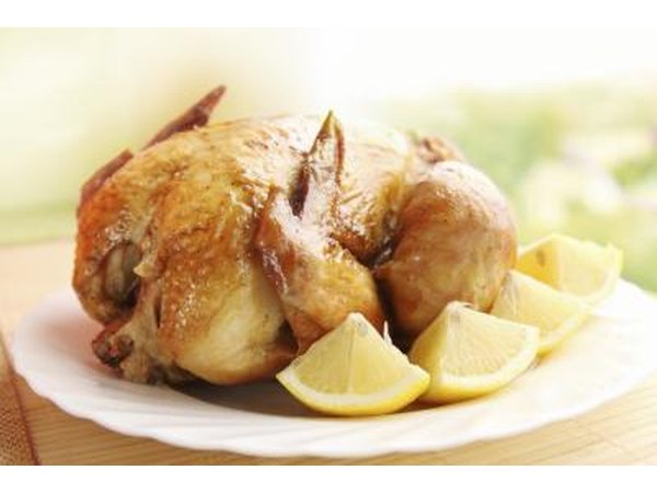 A roasted chicken on a platter with fresh lemon wedges.