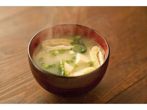 A steaming bowl of miso soup on the table.
