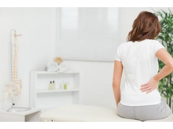 Back pain is the most common symptom.
