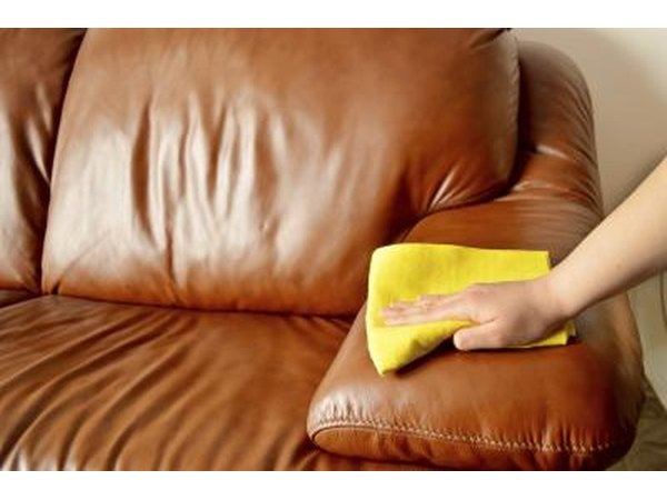 A woman wipes a leather sofa with a soft cloth.