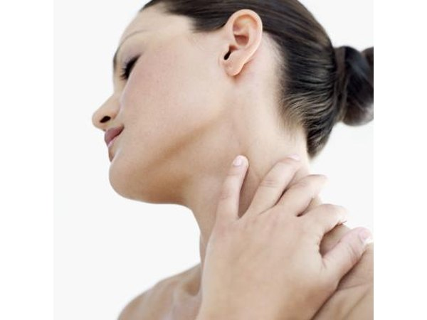 A woman holds her swollen neck.