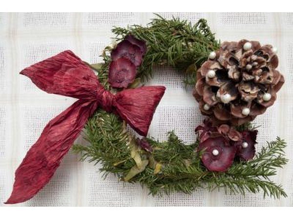 Homemade wreath with ribbon and a pinecone.